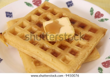 A plate of waffles with syrup and butter.