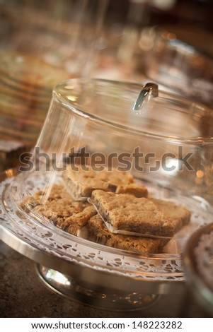 A plate of warm cookies with a glass covering