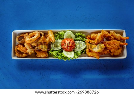 A plate with deep-fried spicy golden calamari rings and tasty shrimps with vegetables. - stock photo