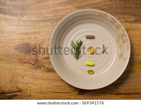 A plate with dietary supplements over aged wooden board is ready to be consumed, Asian style - stock photo