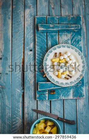 A plate with mozzarella balls and pineapple sliced  served on blue vintage chalkboard from above. Rustic style. - stock photo