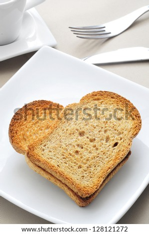 a plate with two bread rusks forming a heart on a table with a cup of coffee - stock photo