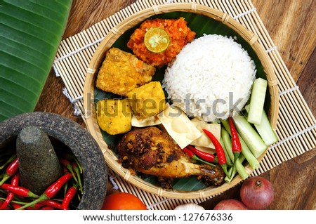 A plates of Delicious 'Ayam Penyet' with 'Sambal Belacan' and 'Tempe'- local flavor - stock photo