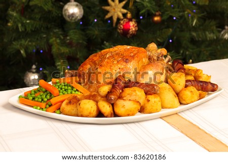 A platter containing a christmas dinner with a christmas tree in the background - stock photo