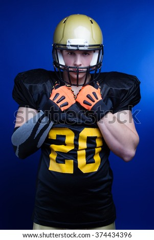 A player in american football with helmet on his head standing on blue background. - stock photo