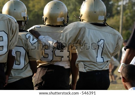 A player puts his hand on the shoulder of one of his teammates; showing boyish affection. - stock photo