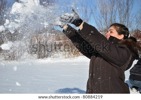 A playful woman enjoy a day outside with snow