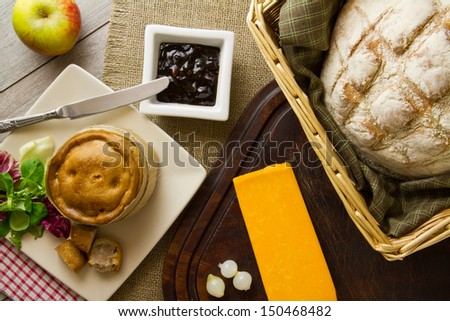 A ploughmans lunch fare, spread out on burlap, bread board and distressed boards. Melton Mowbray pork pie with artisan boule bread in basket, next to red Leicester cheese, butter, salad and an apple.