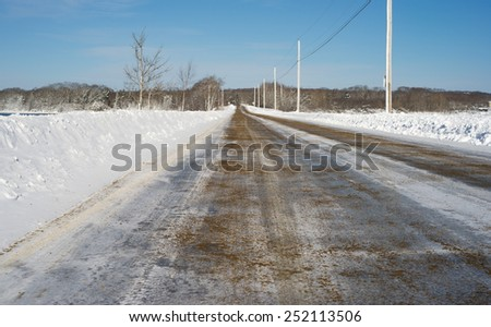 A plowed road with sand strewn on the icy surface for traction in Maine.