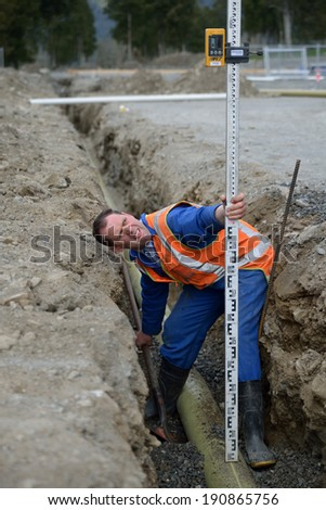 a plumber aligns pipes in a drainage trench at a large industrial building site - stock photo