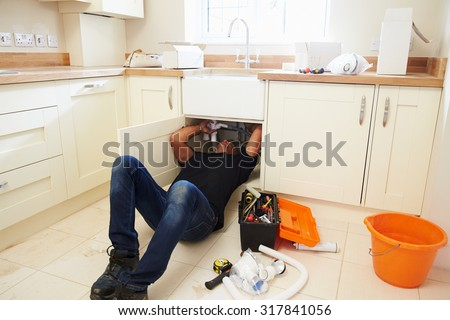 A plumber lying on his back to fix a kitchen sink - stock photo