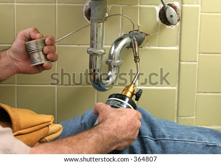 A plumber using a welding torch to solder a pipe.