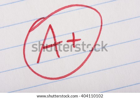 A plus (A+) grade written in red pen on notebook paper. - stock photo