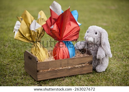 A plush rabbit holding a basket of brazilian Easters eggs on the grass. - stock photo