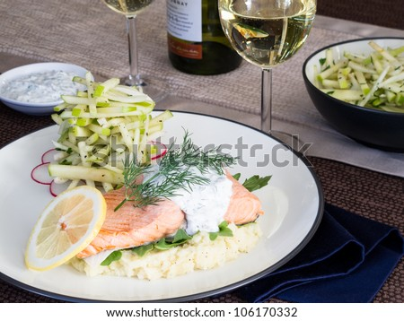 A poached salmon sits atop a bed of parsnip puree and arugula accompanied by a fennel and green apple salad and Chardonnay wine. - stock photo