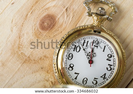 a pocket watch on a wooden background