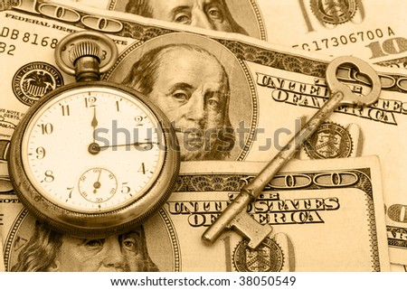 A pocket watch sitting with an antique key on a hundred dollar bill background, time management - stock photo