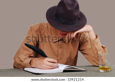 A poet writing on desk with the glass beside - stock photo