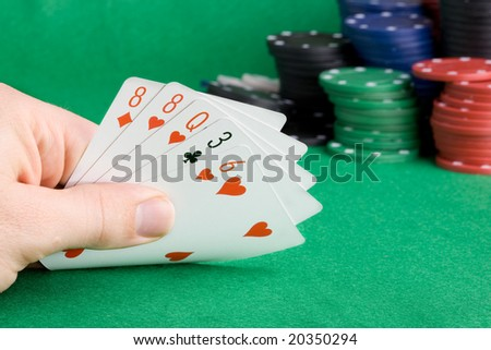 A poker hand with one pair - a poker player looking at his cards