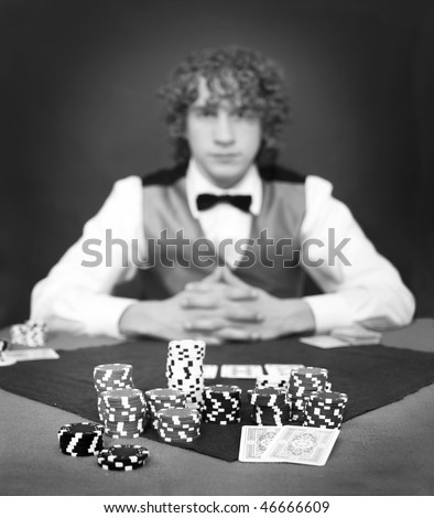 A poker player facing the dealer over a stack of chips. Shallow DOF, focus on the front row of chips - stock photo
