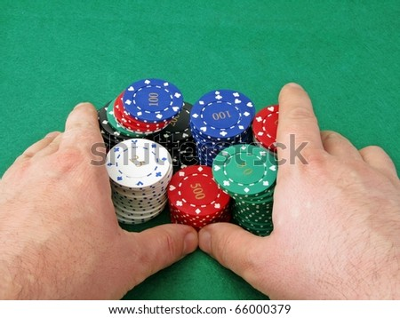 A poker players hands pushing in all his chips on a green felt background - stock photo