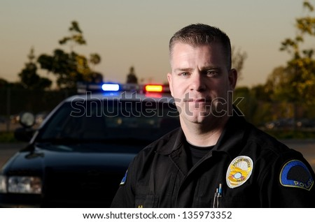 A  police K9 officer in front of his patrol car. - stock photo