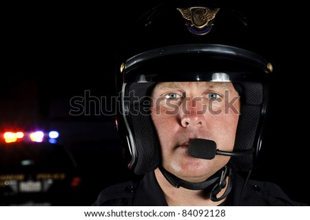 a police motorcycle officer in the night. - stock photo