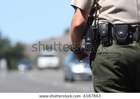 A police officer standing by traffic - stock photo