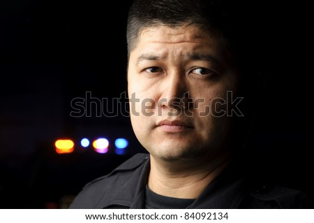 a police officer standing in the night with his police car in the background. - stock photo