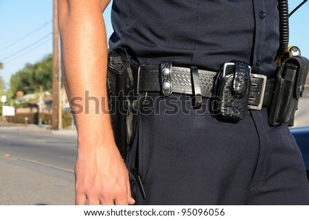 a police officer standing in the street next to his car. - stock photo