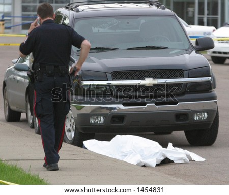 A policeman makes a cell call while standing beside a shooting victim. - stock photo
