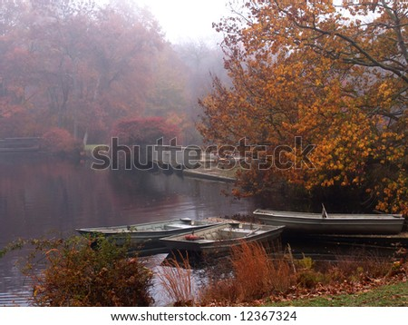 A pond, rowboats a small concrete bridge and the colors of fall muted by the morning fog. Connetquot River State Park Preserve, Long Island, New York.