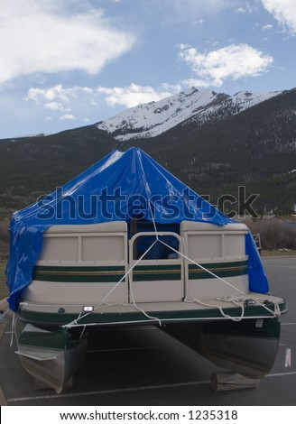 a pontoon boat stored in the mountains of colorado covered with a blue plastic