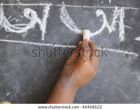 A poor kid in India learning to write alphabets. - stock photo