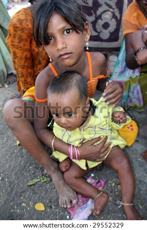 A poor streetside girl holding her toddler brother, in India.