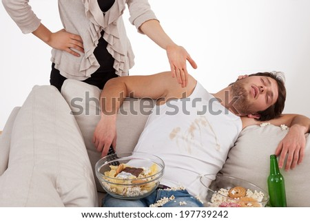 A poor wife and a lazy sleeping dirty husband in a mess - stock photo