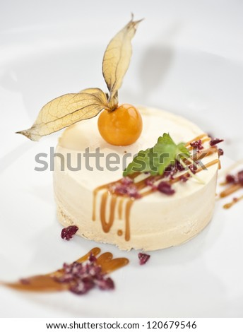 A portion of caramel parfait with a physalis and some mint on top - stock photo