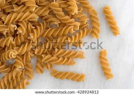 A portion of fusilli whole wheat organic pasta on a marble cutting board. - stock photo