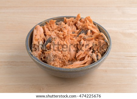A portion of Pacific canned pink salmon in an old stoneware bowl atop a wood table.