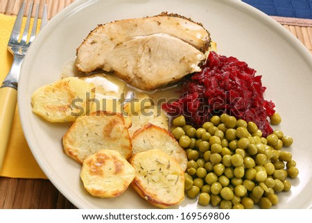 A portion of roast turkey breast with baked potatoes, beets and peas - stock photo