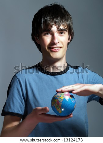 A portrait about a trendy attractive travel agency agent guy who is smiling, he is holding a globe in his hands and he is planning a travel for a client. He is wearing a blue t-shirt. - stock photo