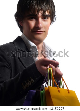 A portrait about a trendy attractive young man who is smiling and he is holding some shopping bags. He is wearing a white shirt and a stylish black suit. - stock photo