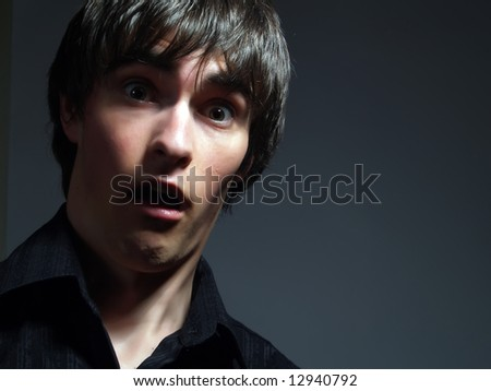 A portrait about a trendy handsome young man who is looking towards and he is surprised or scared. He is wearing a stylish black shirt. - stock photo