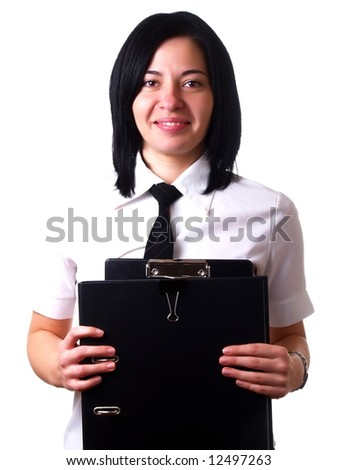 A portrait about a young pretty happy businesswoman with black hair who is holding some folders at the office and she is wearing a white shirt and a black tie
