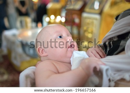 A portrait of a baby boy during christening ceremony on a golden background of church. This photo has a shallow depth of field and the focus is on his eye - stock photo