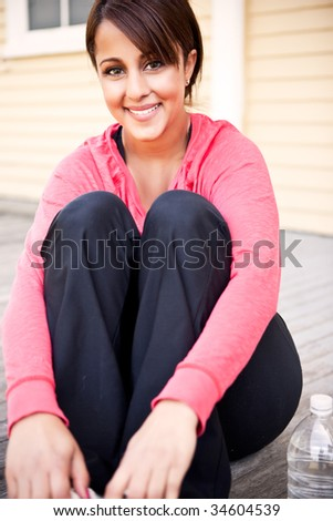 A portrait  of a beautiful asian woman sitting after exercising - stock photo
