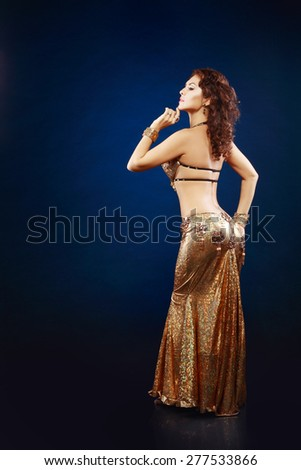 A portrait of a beautiful belly dancer over dark background