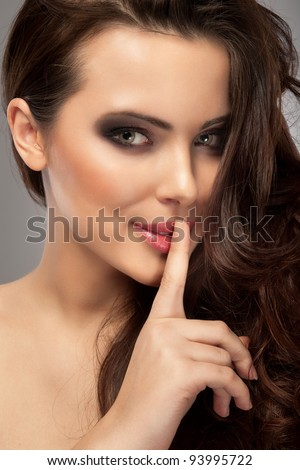 a portrait of a beautiful brunette with a finger on her lips showing to keep silence, hush - stock photo