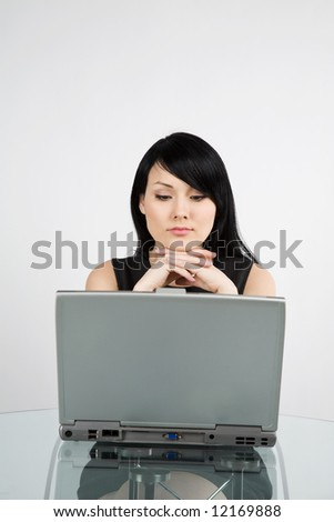 A portrait of a beautiful businesswoman working on her laptop at the office - stock photo