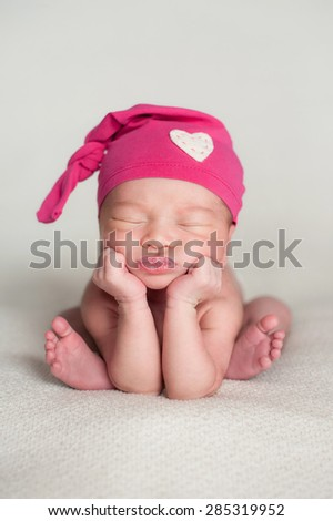 A portrait of a beautiful eleven day old baby girl wearing an up-cycled pink top knot cap with heart detail. She is sleeping on a beige blanket and posed with her chin in her hands.